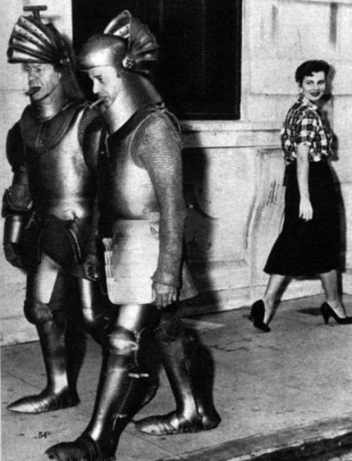 Two guys walking around in armor near a woman