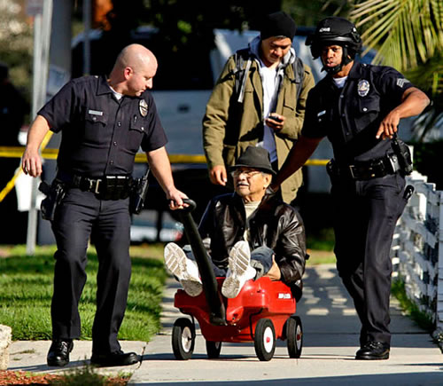 Old man being led away by police in a red wagon
