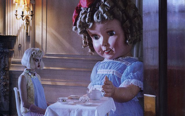 Woman has tea party with giant doll