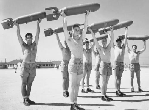 Shirtless guys lifting missiles