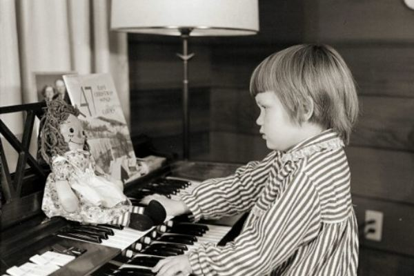 Kid plays organ while Raggedy Ann watches