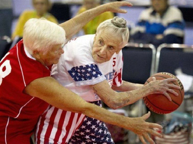Older woman in USA outfit keeps basketball away from older woman in Soviet red outfit.