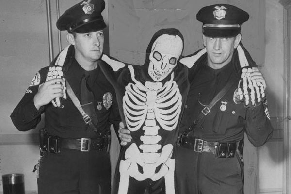Guy in a skeleton costume is taken into custody by police