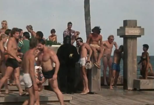 People at a beach - and a guy in a gorilla suit