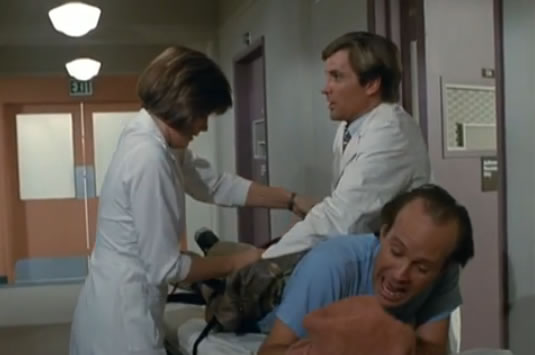 Murdock is wheeled away on a gurney