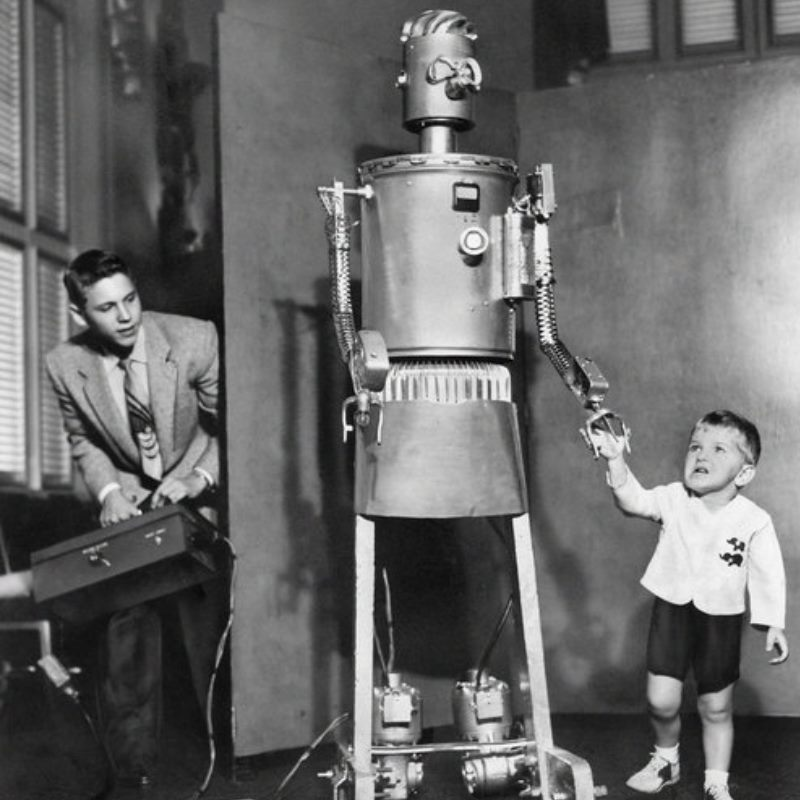 "Child holds hands with robotic ""mom"" while a man operates controls in the background."