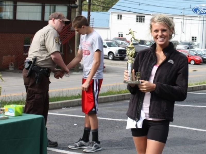 Woman poses with trophy while police officer arrests a man in the background.