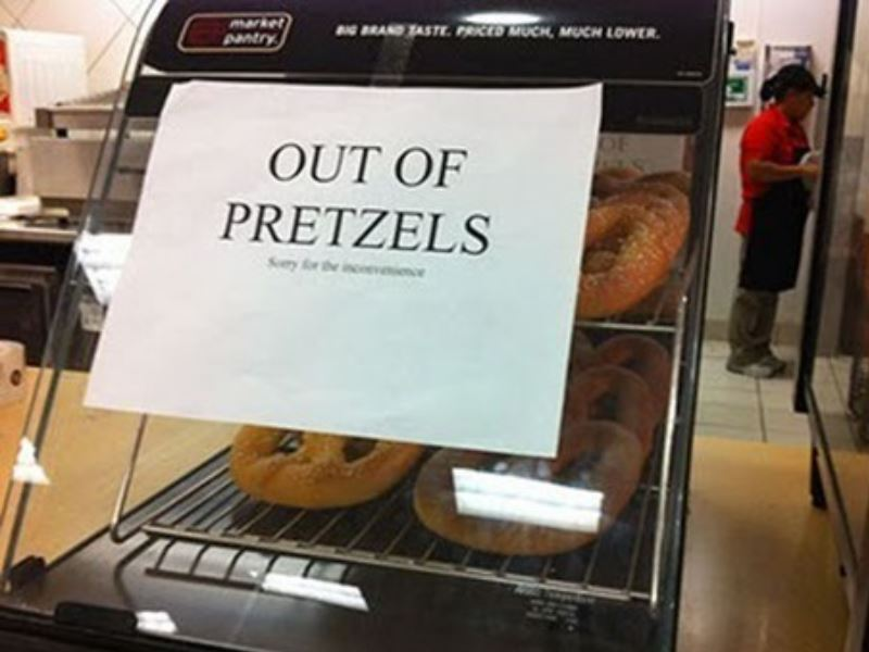 "A vending box with pretzels in it is labeled ""out of pretzels"""
