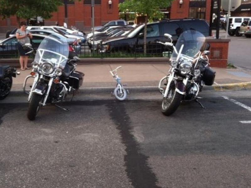 A kid bicycle is parked in between two large and imposing motorcycles.