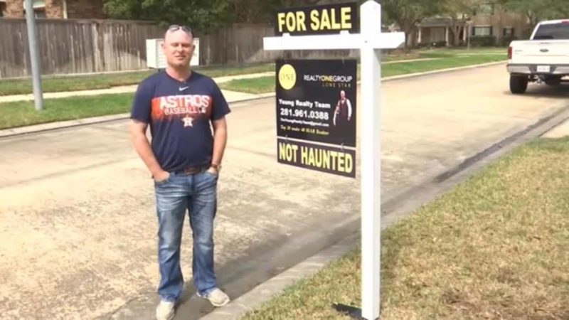"Realtor standing next to a sign that says ""For sale: not haunted"""