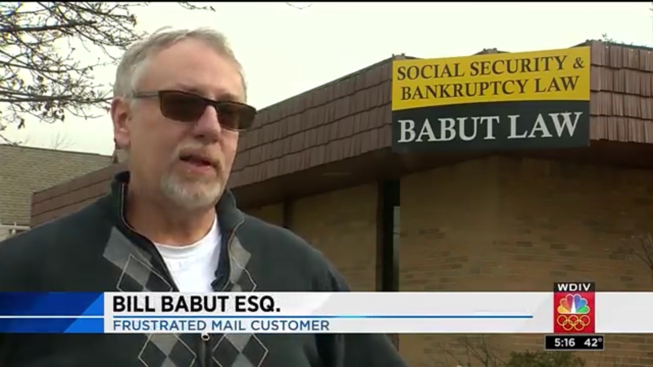 "Bill Babut Esq.: Frustrated Mail Customer. In the background is a sign for ""Babut Law"""