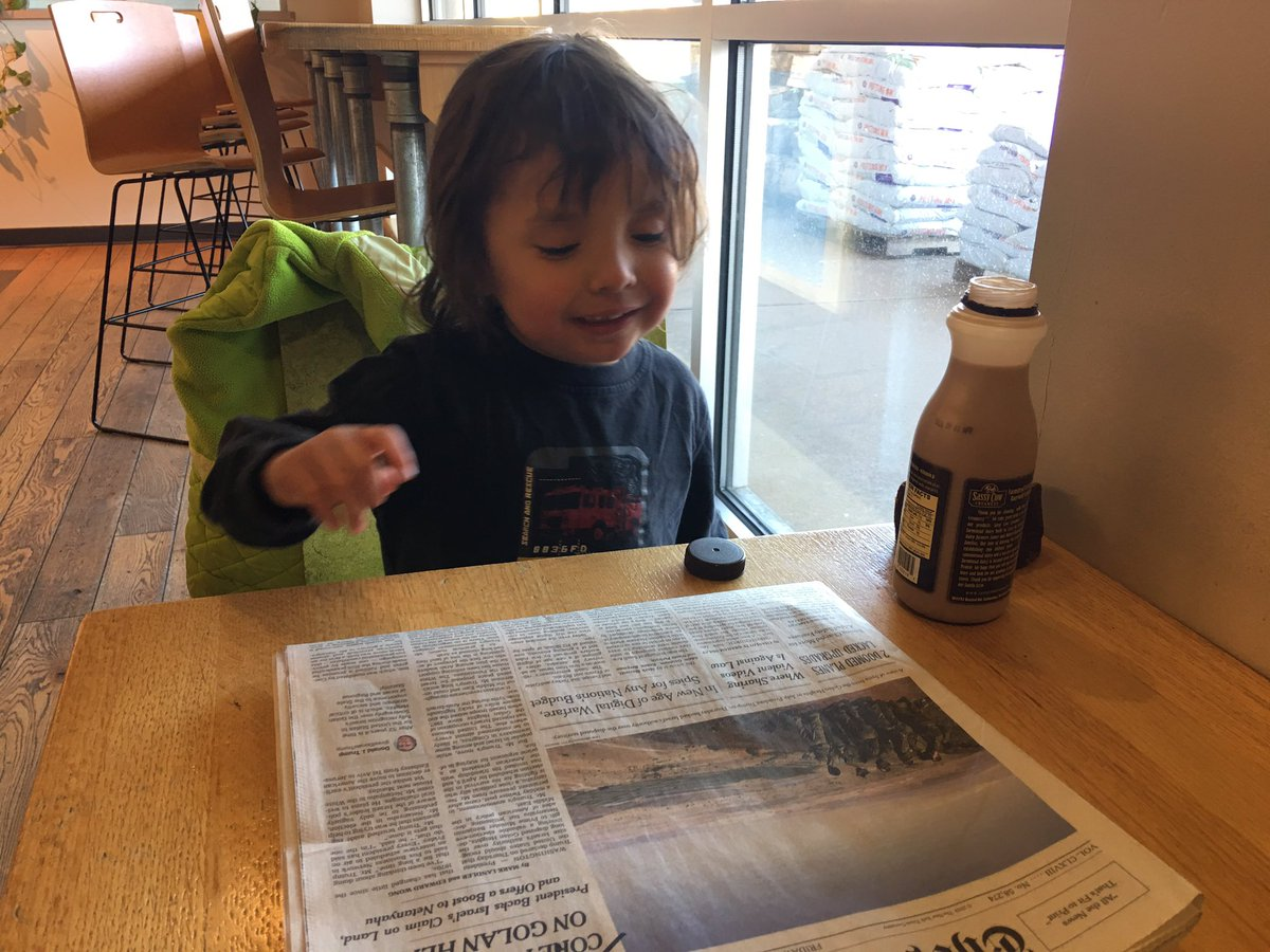 Four year old drinking chocolate and reading the newspaper