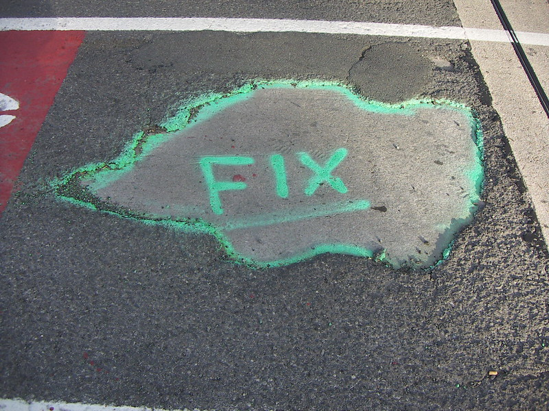 """Pothole with the word """"FIX"""" spray painted on top (photo by Deborah Fitchett via Flickr/Creative Commons https://flic.kr/p/7EyMVT)"""