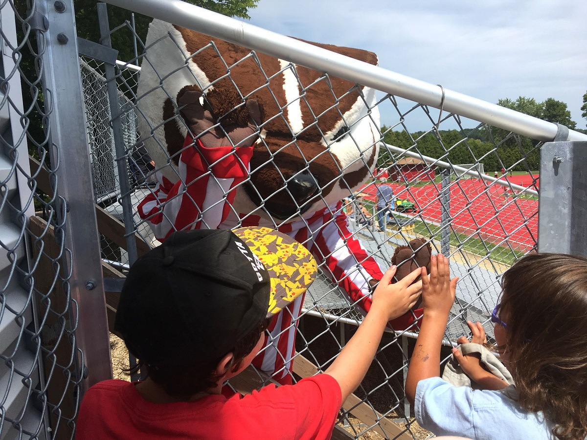 Eight year old and four year old high-five Bucky through the fence