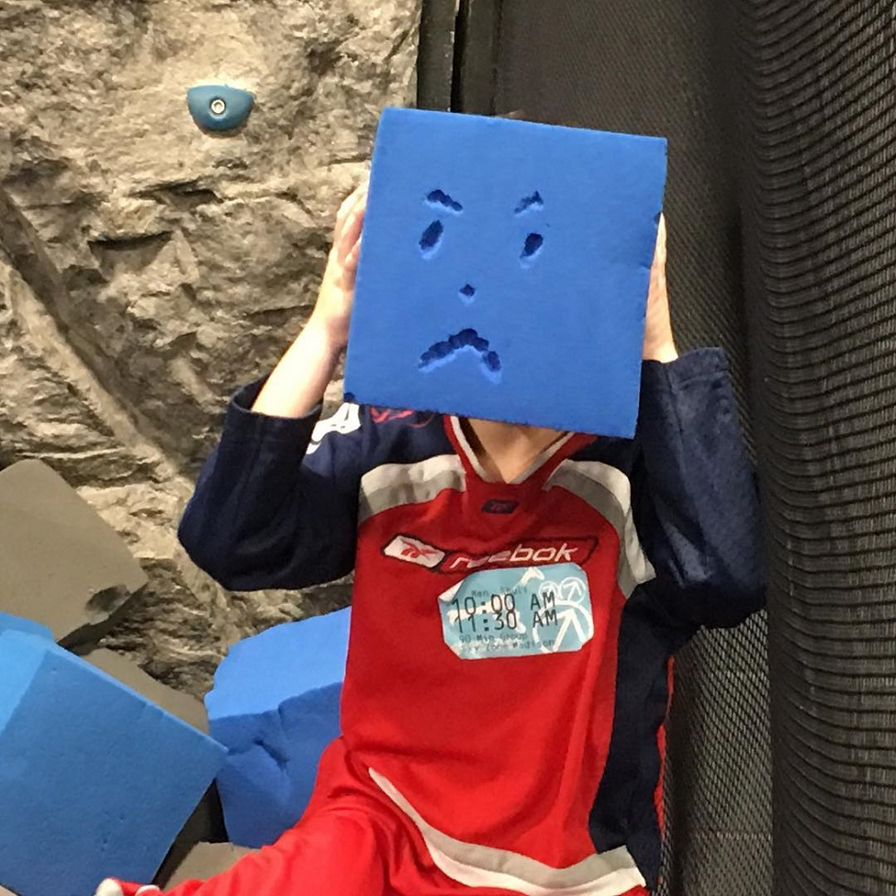 Seven year old holds up a big foam block with a grumpy face on it