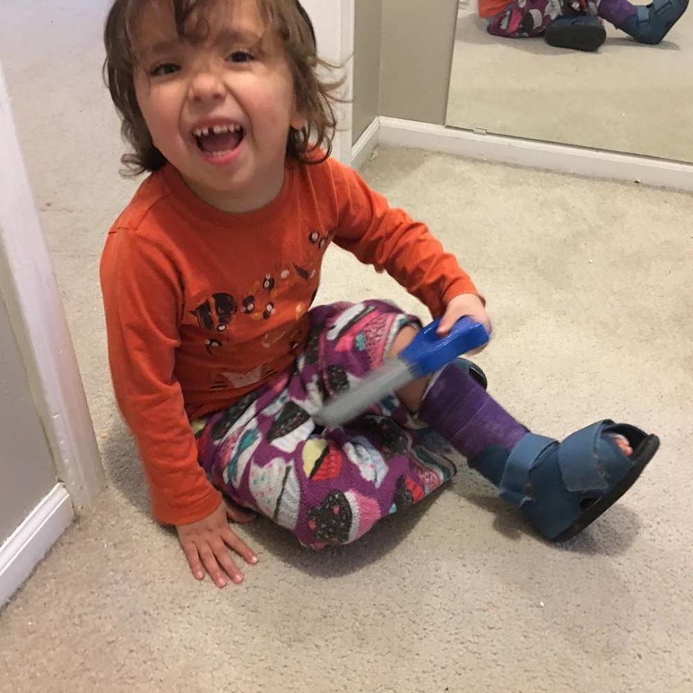 Three year old laughs as he pretends to saw his leg off