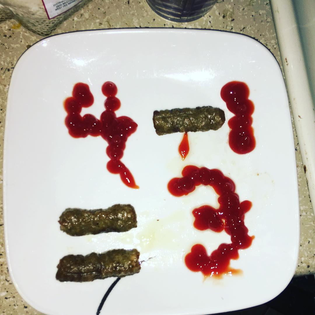 """The plate spells out """"4 - 1 = 3"""" in sausage and ketchup. It looks creepy."""