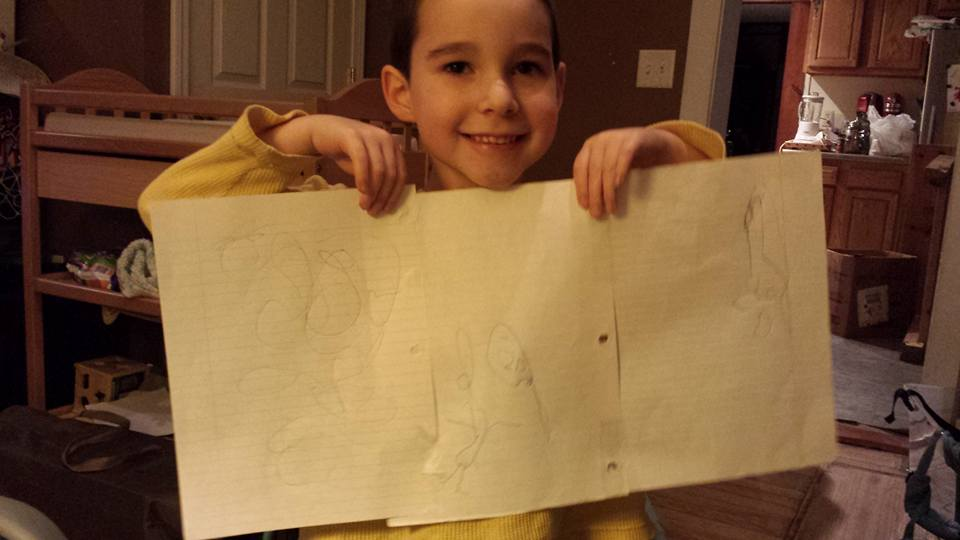 Four year old holds up his drawings