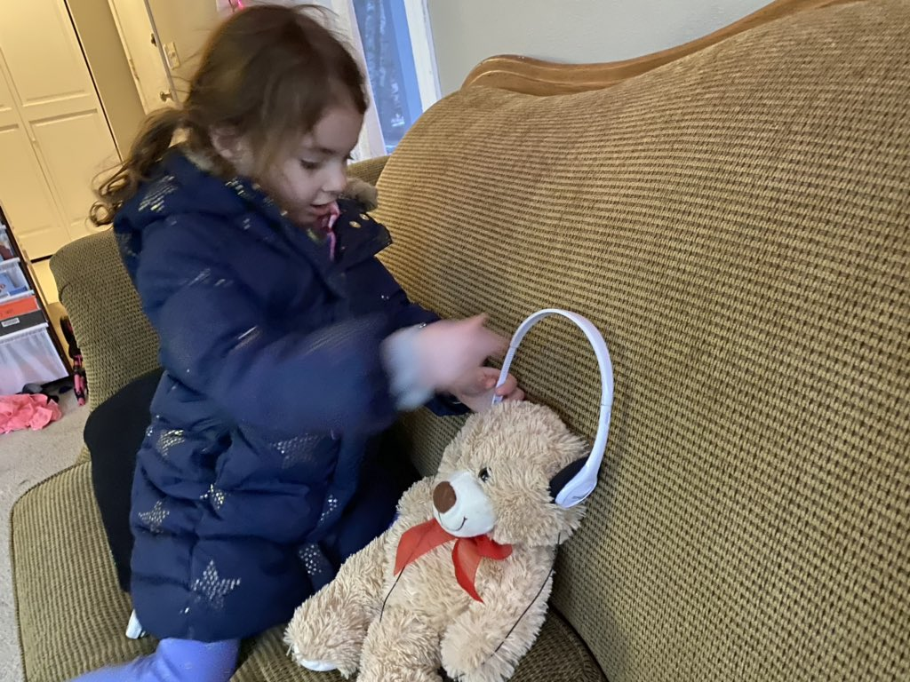 Four year old puts headphones on her teddy bear