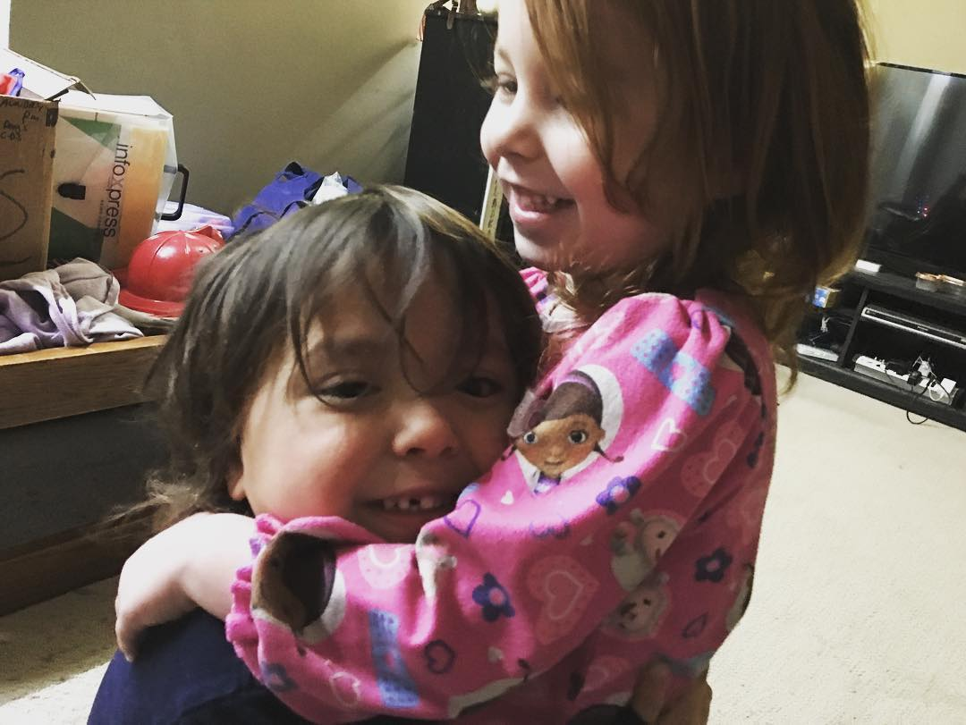 Three year old gets hugs from her bro
