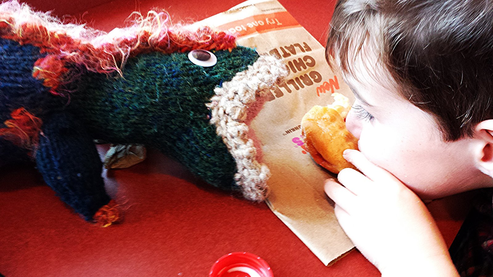 The boy and his toy T-rex eat a doughnut