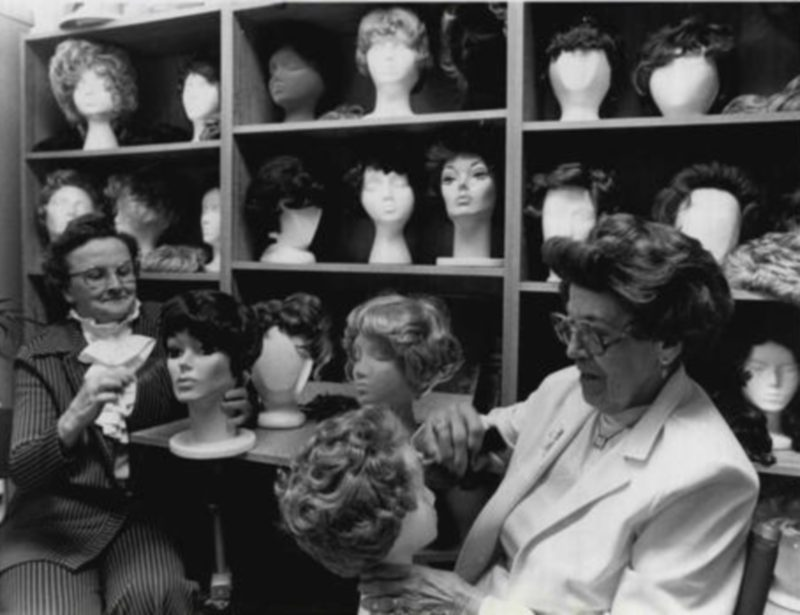 Two older women with lots of mannequin heads.