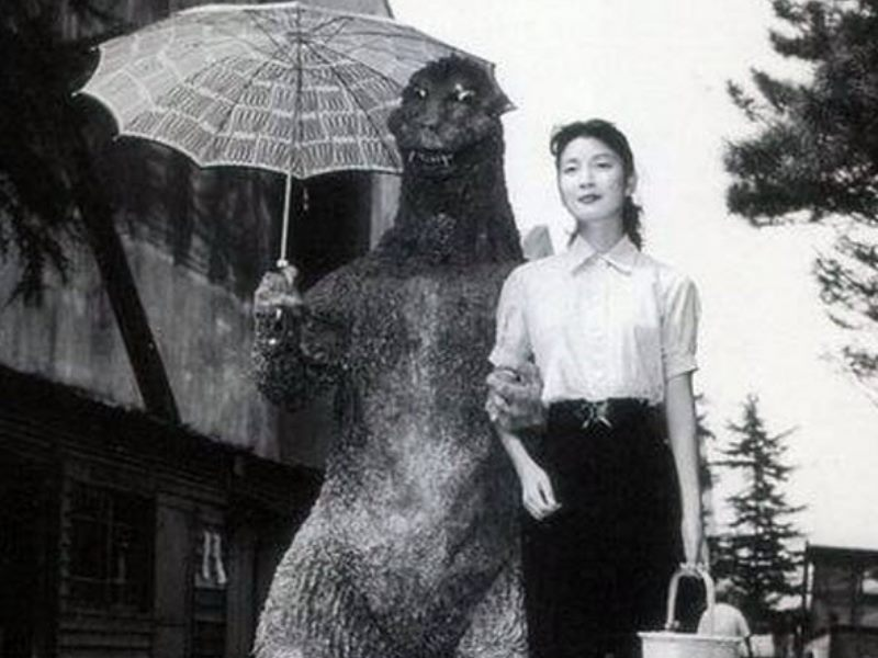 Godzilla takes a woman for a walk, while holding an umbrella