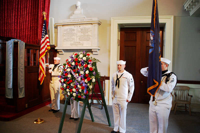 Members of the US Navy stand next to the wreath for John Quincy Adams.