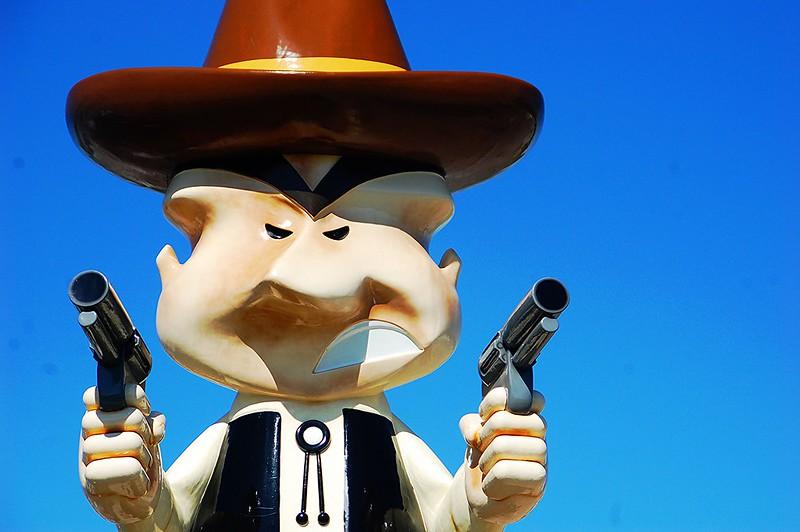 Close-up of a cartoon cowboy statue holding two guns