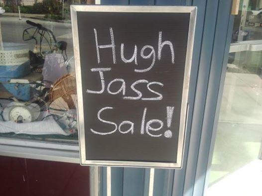 """Sidewalk sign says """"Hugh Jass Sale!"""""""