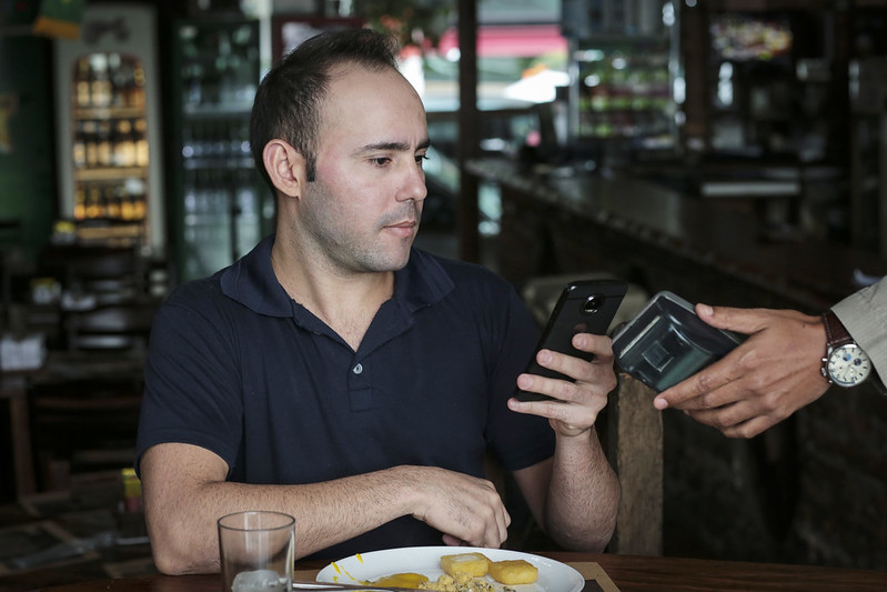 A man at a cafe has his phone out; there's a hand holding another phone right by his. (Photo by Sebrae-SP via Flickr/Creative Commons https://flic.kr/p/26VKxhA)
