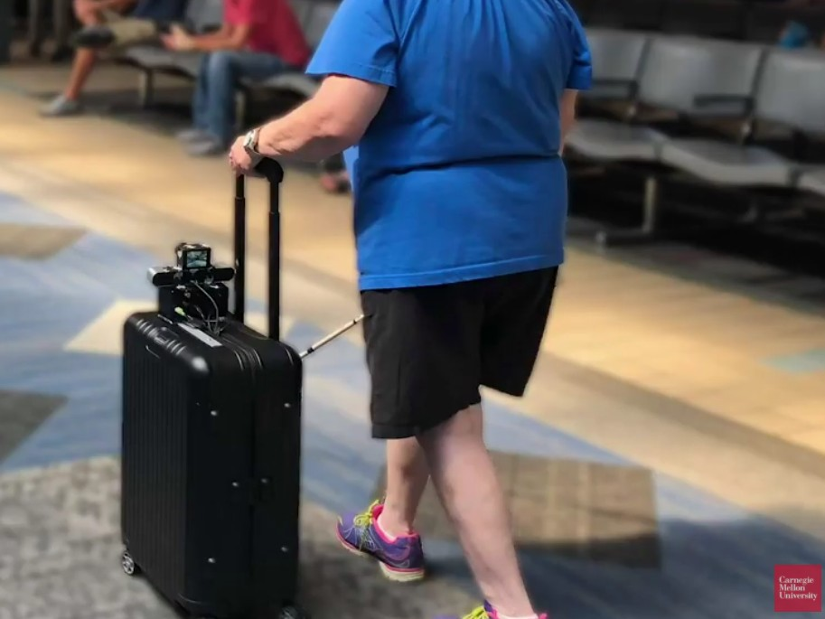 A woman uses the smart suitcase in an airport while also using a cane. (Screenshot from video by Carnegie Mellon University https://www.cmu.edu/news/stories/archives/2019/may/suitcase-helps-navigate-airports.html)