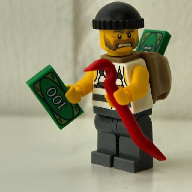 A Lego burglar minifig is walking away with some Lego money. (Photo by Martin @pokipsie Rechsteiner via Flickr/Creative Commons https://flic.kr/p/q23Jfy)