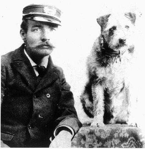 Owney the dog (right) with a railroad worker with a bushy mustache, wearing a uniform. (Photo via the National Postal Museum/Creative Commons https://collections.si.edu/search/record/ark:/65665/hm8af75c3179bea4f46958cacc39c349a82)