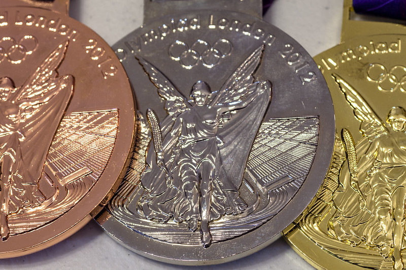 """Bronze, silver and gold Olympic medals, depicting a winged figure in front of an Olympic track stadium. The words """"Olympics London 2012"""" are on the top. (Photo by Paul VanDerWerf via Flickr/Creative Commons https://flic.kr/p/237DGUE)"""