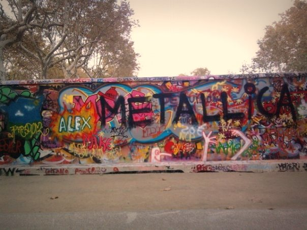 """Someone spray painted """"METALLICA"""" in big black letters on a wall of colorful graffiti. (Photo by Alaska Carter via Flickr/Creative Commons https://flic.kr/p/aGji8P)"""