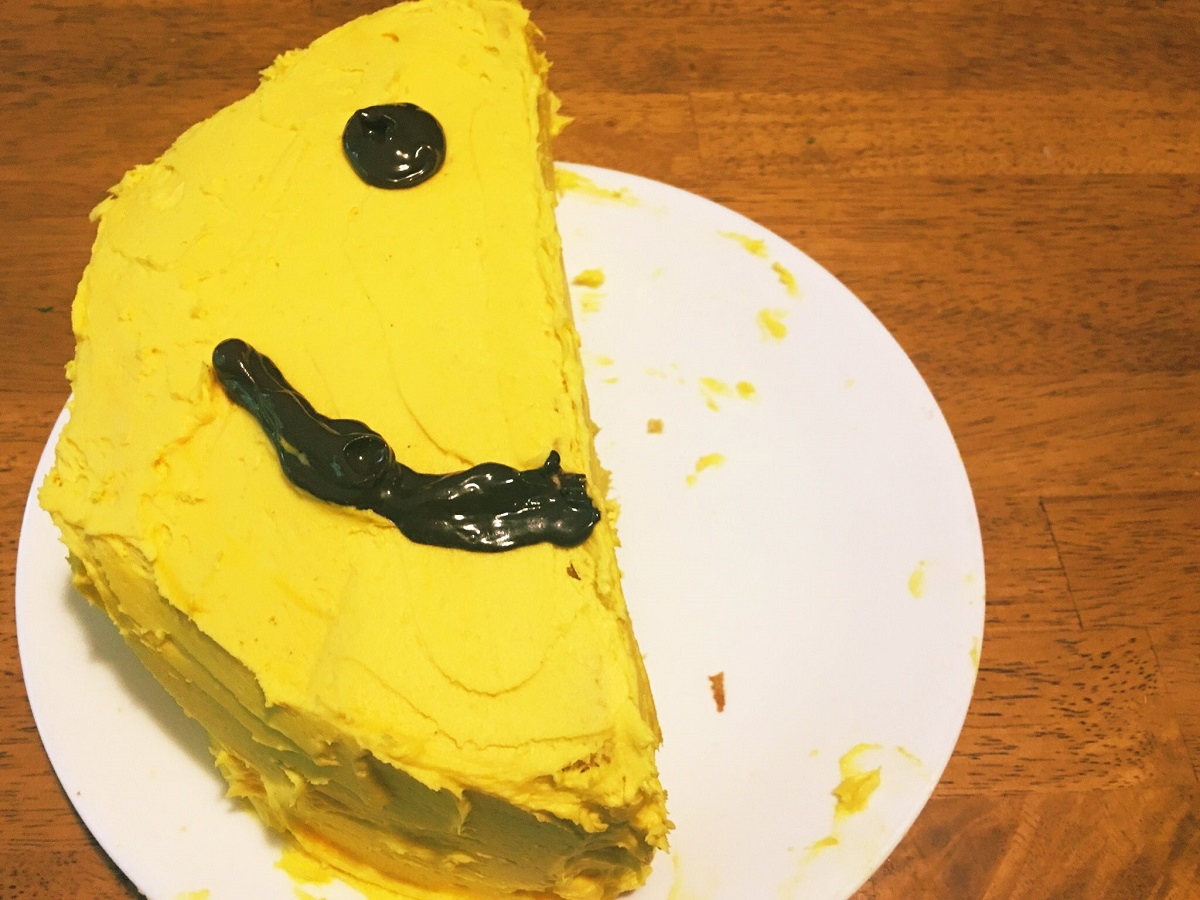 A half cake, with half a smiley face on top
