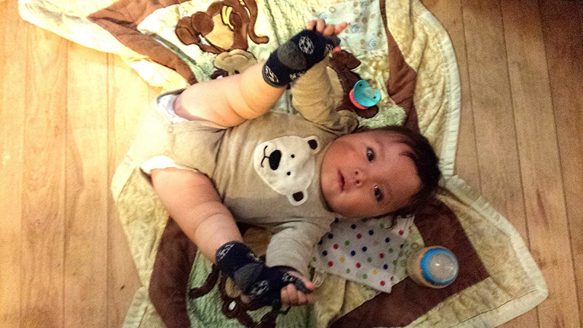"Baby boy in ""happy baby"" yoga pose"