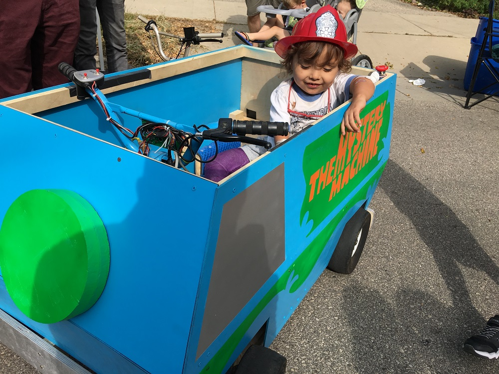 Three year old in a toy Mystery Machine