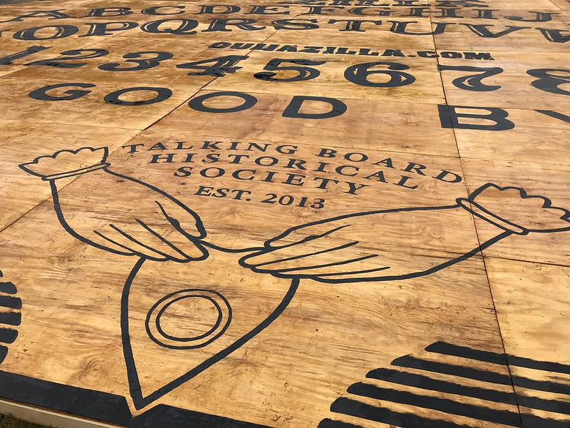 Close-up on part of the giant Ouija board in Salem, MA, showing a pair of hands moving the piece over a board. (Photo by Dex via Flickr/Creative Commons https://flic.kr/p/2hufjUU)