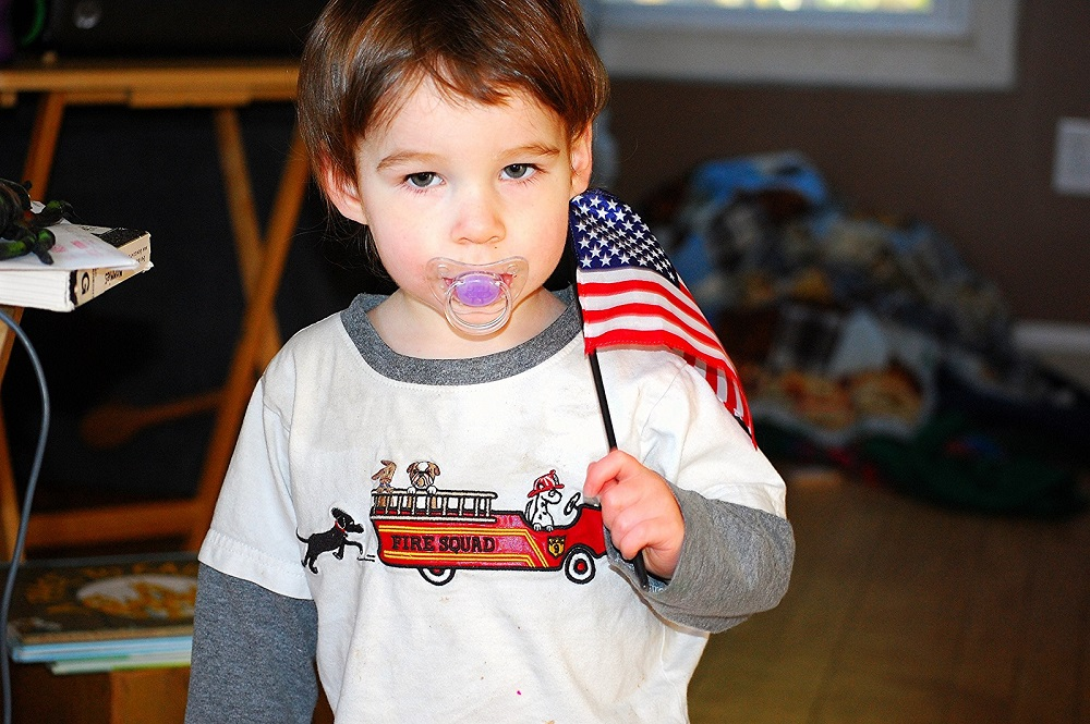 One year old holds a flag