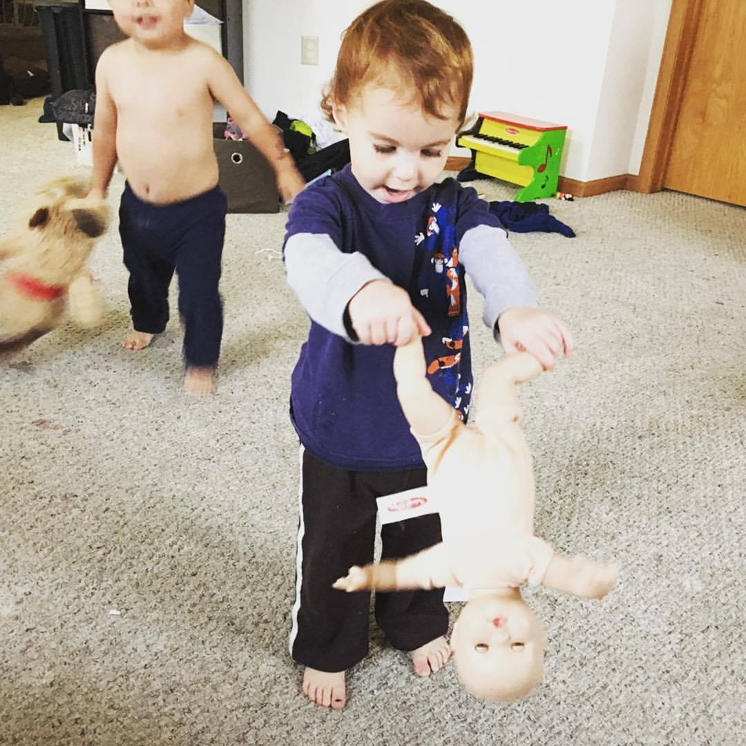 Baby girl puts her doll upside down