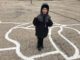 Seven year old stands in a painted map of Wisconsin
