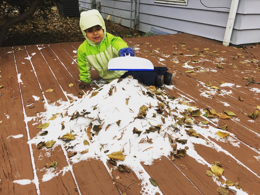 Three year old makes a snow pile on the deck