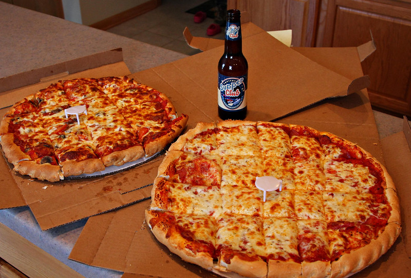 Two round pizzas, cut into square pieces, next to an open bottle of beer. (Photo by Jerry Huddleston via Flickr/Creative Commons https://flic.kr/p/9TLBjx)