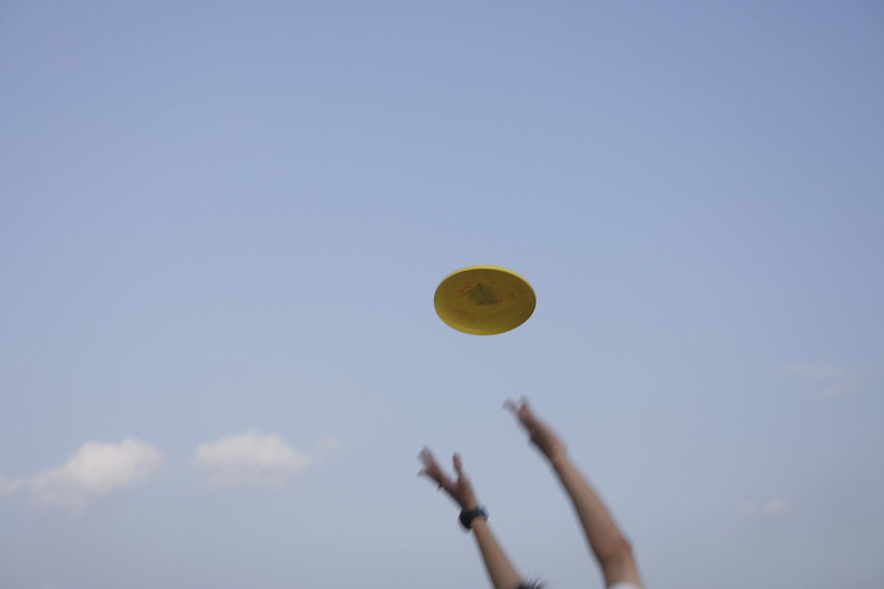 A yellow flying disk heads toward a pair of outstretched hands, trying to catch it. (Photo by nonrev via Flickr/Creative Commons https://flic.kr/p/6Bzgx)