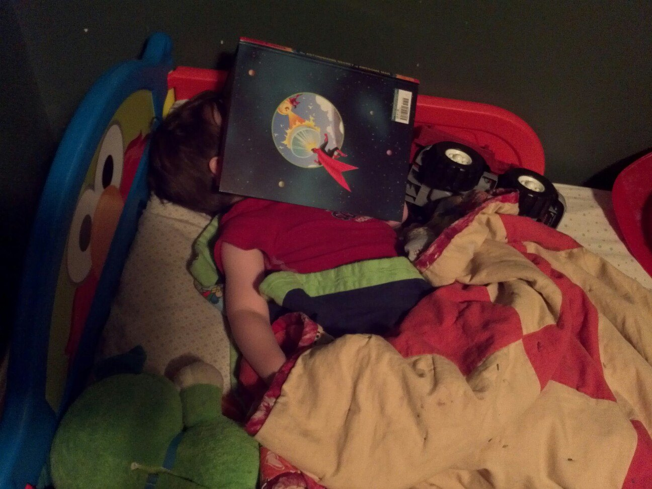 Three year old asleep under a book
