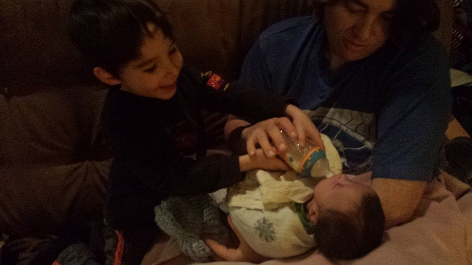 Big brother helps give his baby brother a bottle