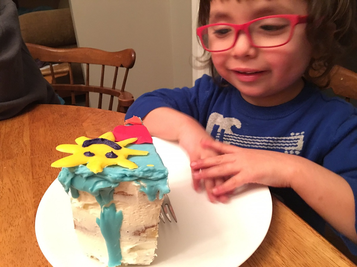 Four year old with a slice of his rainbow cake