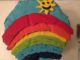 Two layer cake with a rainbow and a smiling sun on it
